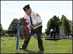 Roger Swinney of American Legion Post 28 places a wreath at the base of the flagpole in Fort Meigs Cemetery during the Memorial Day Remembrance Ceremony today in Perrysburg.