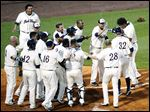 The Mud Hens greet Steven Moya, right, at home plate after his ninth-inning, two-run home run against Buffalo.