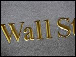 FILE - This Monday, July 6, 2015, file photo shows a sign for Wall Street carved into the side of a building in New York. Stocks are opening slightly higher on Wall Street, Tuesday, May 31, 2016, as the market comes off its best week since early March. (AP Photo/Mark Lennihan, File)