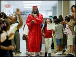 Jay Manning, 18, of Rogers High School walks with first-grader Sherri Hampton, 6, through Robinson Elementary in Toledo. The ceremony on Tuesday honored five former Robinson students who are graduating later this week.