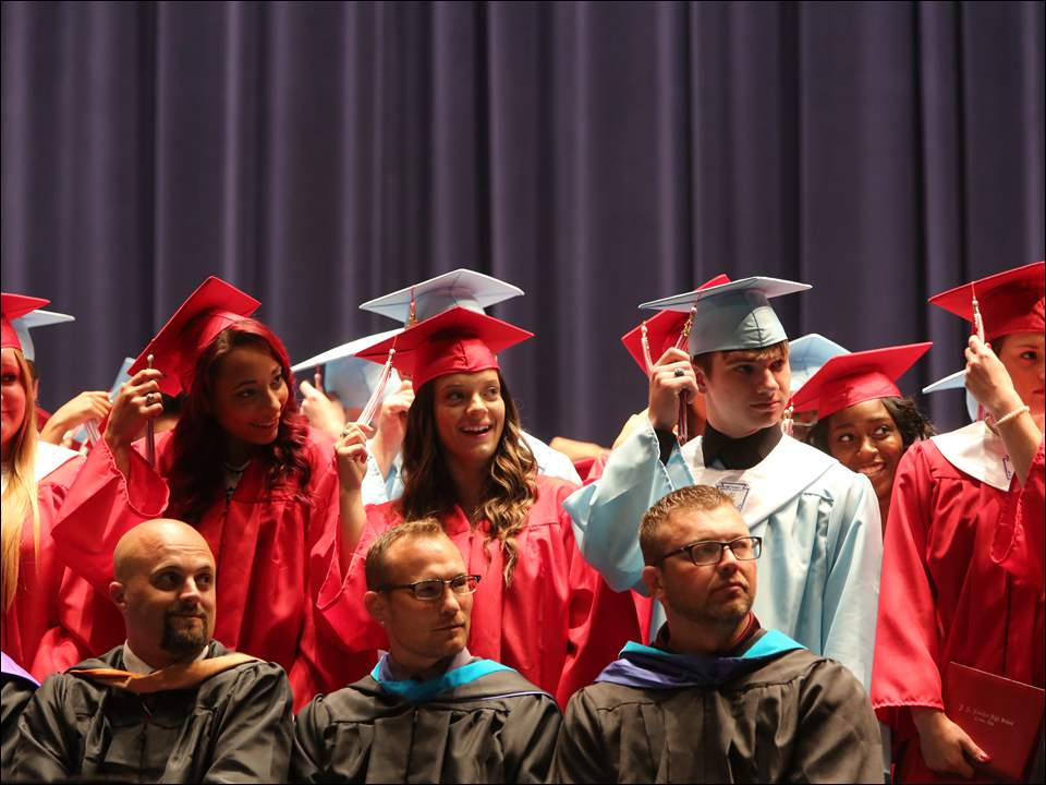 Graduating seniors, standing, prepare to turn their tassels at the end of the ceremony.