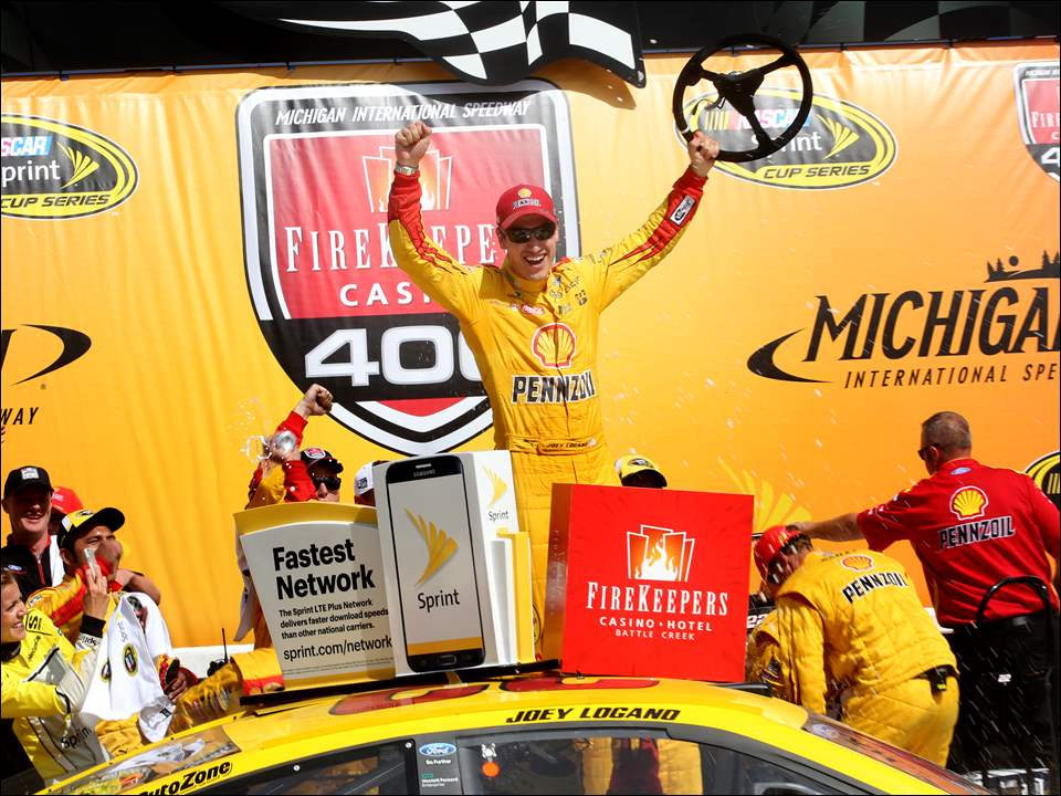 Joey Logano celebrates after winning the NASCAR Sprint Cup series FireKeepers Casino 400.