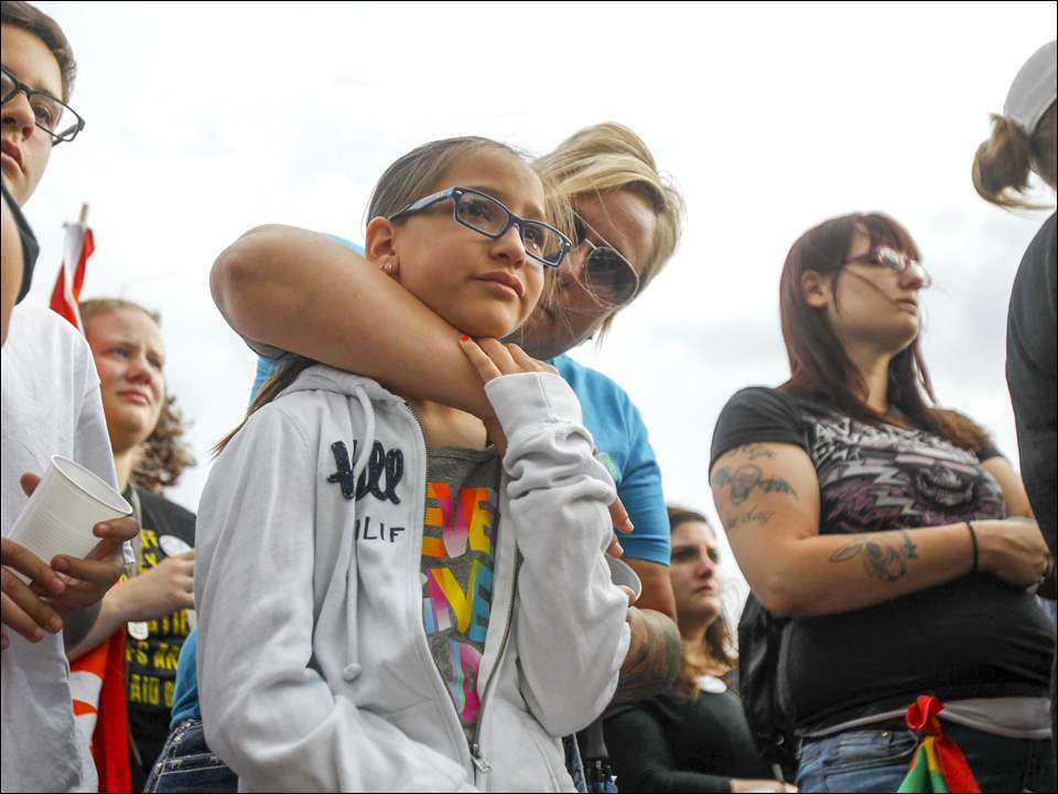 Crowd members hug as victims of the Orlando shooting are read aloud during the Orlando Solidarity Vigil in downtown Toledo, organized by Equality Toledo.