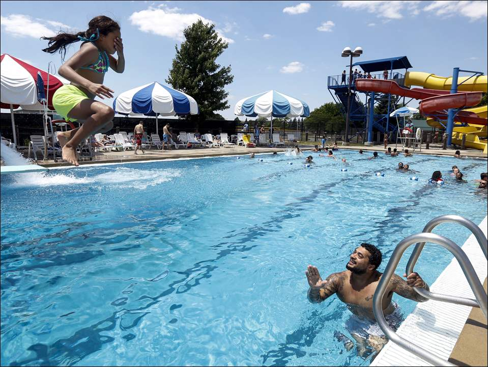 Tyrone Thomas, right, of Toledo, watches while his daughter Tyniyah Thomas, 10, left, jumps off of the diving board.