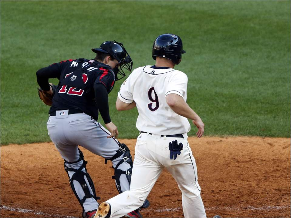 John Hicks crosses home plate before the tag to score for the Mud Hens.