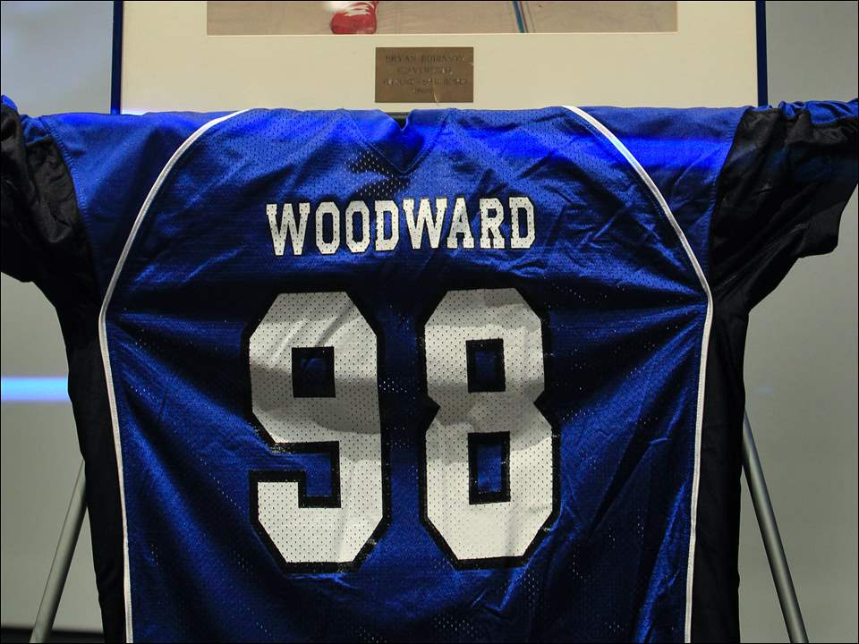 Bryan Robinson's high school wrestling photo and No. 98 Woodward football jersey sit on the stage.