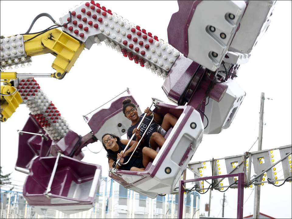 "Mireya Venancio, left, 12, and her friend Yvette Vanlencia, right, 11, of Leipsic, take a ride on the ""Orbiter"" during the Putnam County Fair in Ottawa on June 23."