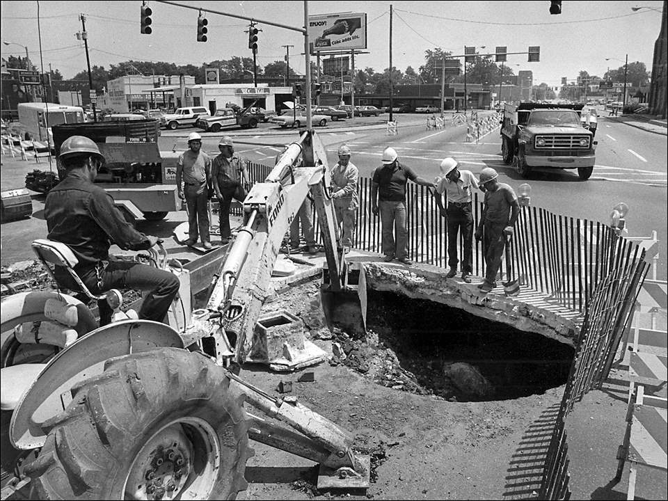"Street crews confronted by city's big 'hole-in-one.' City workers stare into what looks like a bottomless pit at West Bancroft Street and Detroit Avenue Wednesday June 27, 1979. During their efforts to repair the hole, caused by the collapse of an old sanitary sewer. As workers were attempting to clean up ""the hole mess"" Tuesday, another, slightly smaller crater was discovered. The hole has limited traffic on Brancroft to one lane each way at the busy intersection. Officials said repairs will probably take three to four weeks."