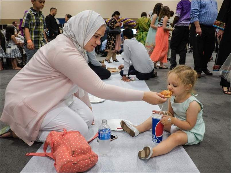 Sommer Matus of Sylvania, feeds a piece of pizza to her daughter Amani Hammuda, 2, during a Unified Eid Prayer and celebration at SeaGate Convention Centre,  Wednesday.