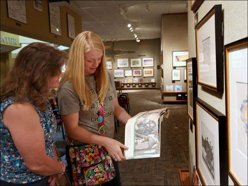 Illustrator Candy Gremler of Perrysburg, left, takes a look at a copy of 'Where the Wild Things Are' with her daughter Samantha near original pieces by the book's author Maurice Sendak at the Mazza Museum.
