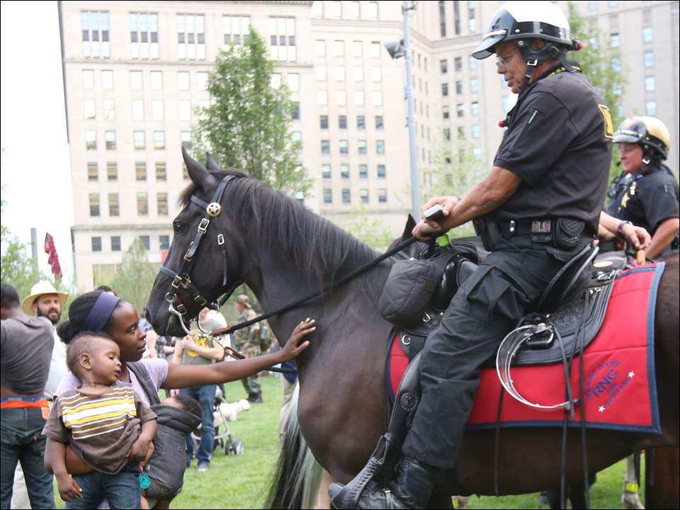 Cleveland resident Lachelle Jordan, left, holds her children Austin, 1, and Amria, 1, as she pets the police horse ridden by Capt. Dave King from Medina County.