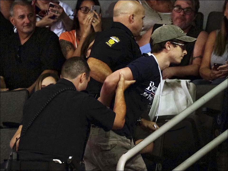 A protester is removed from the arena before a rally for Donald Trump.
