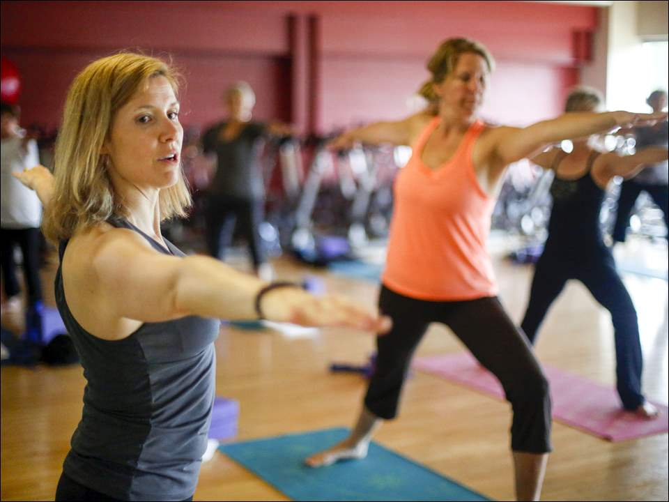 Instructor Ann Heckler, left, conducts yoga class at Wildwood Athletic Club.