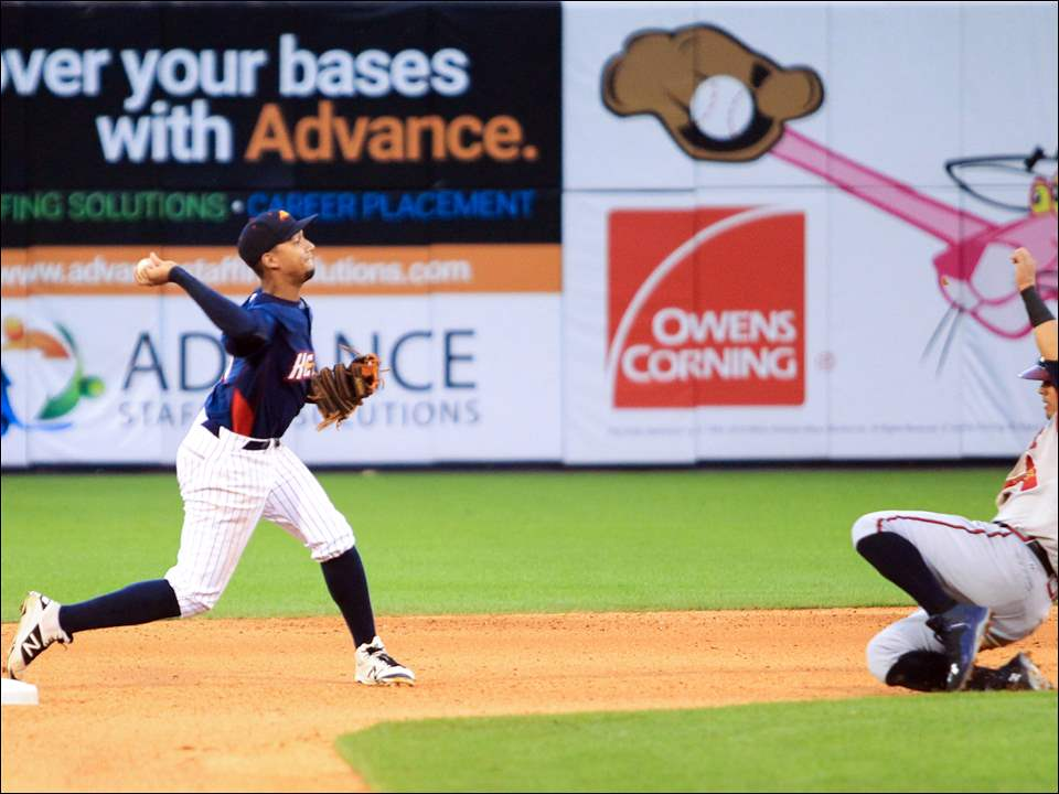 Mud Hens shortstop Dixon Machado throws to first base to complete a double play around the slide of Gwinnett's Rio Ruiz.