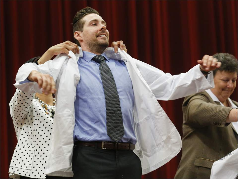 Justin Creeden of Middleborough, Mass., is cloaked by Dr. Iman Mohamed, professor of medicine, during a 'white coat ceremony' as the University of Toledo College of Medicine and Life Sciences, the former Medical College of Ohio, welcomed new medical students Thursday at UT's Nitschke Auditorium.