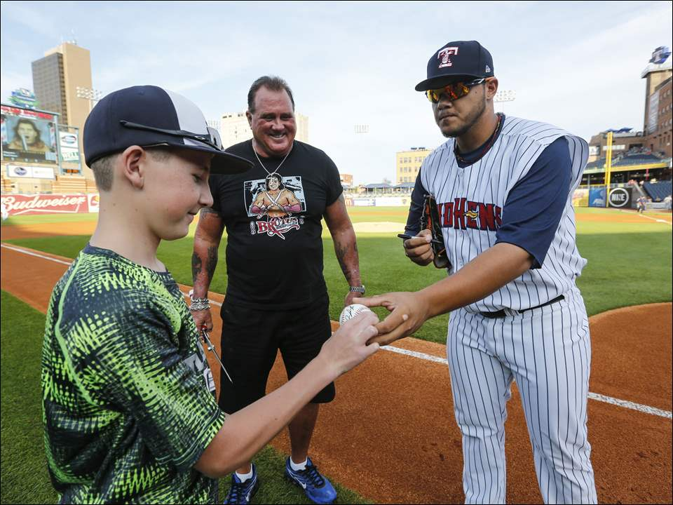 "Mud Hens player Joe Jimenez signs an autograph for Brody Weimer, 13, Carleton, Mich., after throwing out the first pitch for former pro wrestler Brutus ""The Barber"" Beefcake."