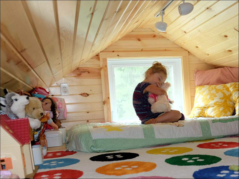 Jane Rye, 3, hugs her stuffed animal as she sits on her loft bed in her family's 360-square-foot tiny house.