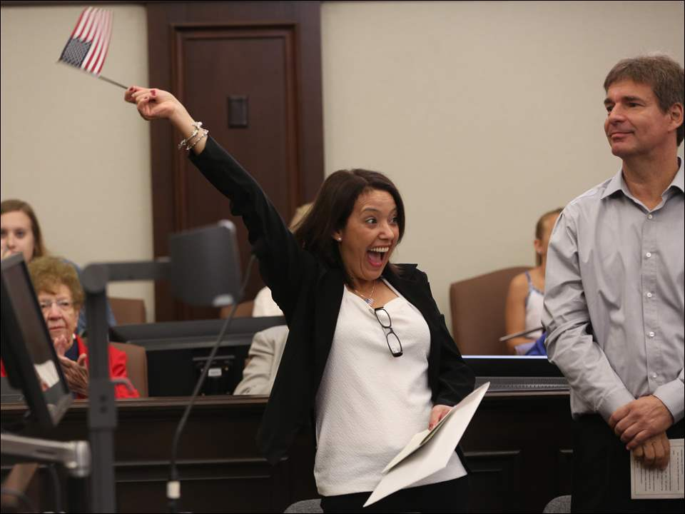Claudia Bernardes Amaral of Brazil celebrates after taking the oath of citizenship during the proceedings. At right is Frederic Andry, formerly of France.