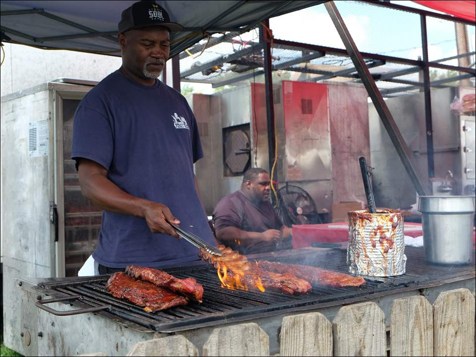 Willie Pruitt grills ribs for Porky Chicks BBQ of Fayetteville, Ark., at The Blade's 33rd annual Northwest Ohio Rib Off at the Lucas County Fairgrounds. Area residents and not-so-local vendors made their way to the event on Friday to try out a variety of barbecue.