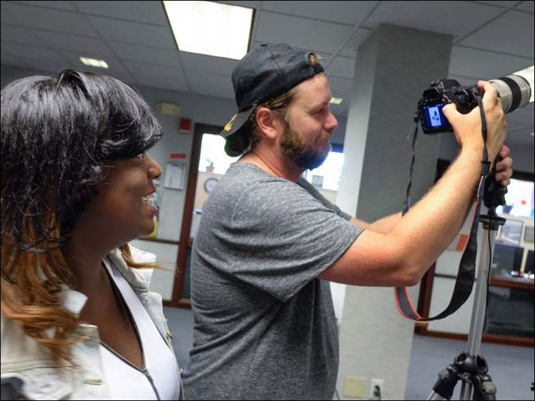 Shakyler Mitchell, 20, reviews her photo with photographer Chris Schooler during the launch of the Head Full of Dream Initiative at the Polly Fox Academy Friday.