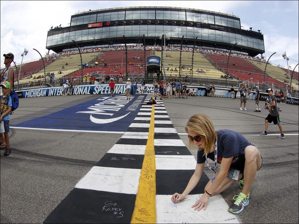 McKinzie Elchert, Sylvania, signs her name to the start/finish line before the NASCAR Sprint Cup Series Pure Michigan 400 at Michigan International Speedway.