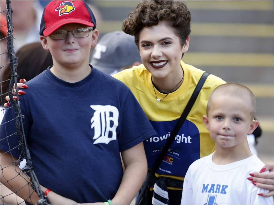 Teen cancer survivor and America's Got Talent finalist Calysta Bevier, center, 16, of Grand Rapids, poses with Mark Mackowiak, 10, left, of Toledo, who is battling Burkitts Cancer, and his brother Ben Mackowiak, right, who was celebrating his 7th birthday, before the Toledo Mud Hens game against the Indianapolis Indians at Fifth Third Field on August 28.