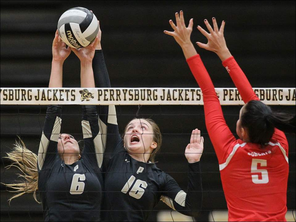 Perrysburg's Morgan Bunde (6) and Kathleen Beer (16) hit the ball against Bowling Green's Kendal Glandorff during a volleyball match at Perrysburg. The Bobcats won 3-1.