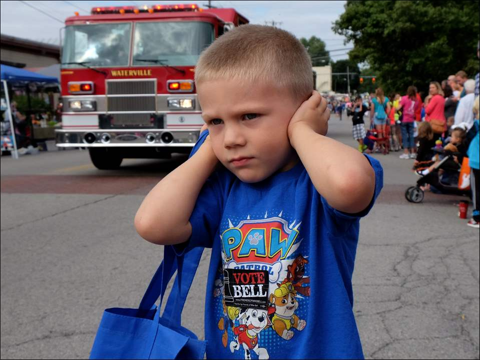 Waterville resident Mason Stroshine, 4, shields his ears from the fire truck sirens.