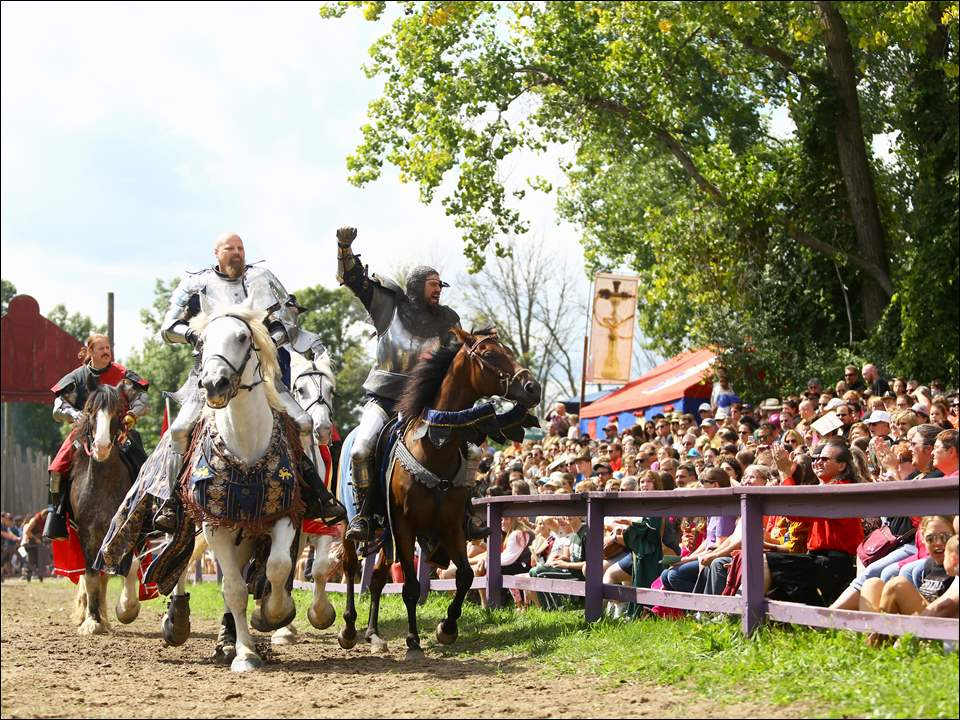 Members of the Knights of the Black Rose jousting troop enter the jousting arena for the first show of the day during the Michigan Renaissance Festival in Holly Michigan.