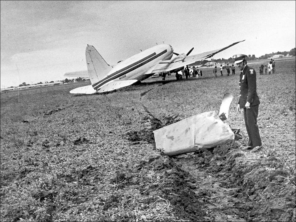 Patrolman Thomas Van Camp eyes the wreckage at the scene on Sunday October 1, 1972 after a Curtiss C-46 Commando WWII surplus transport plane made an emergency landing in field of Mr. and Mrs. Joseph Keil's farm at Reynolds Rd. and Hill Ave. Due to damage, legal entanglements, and simple confoundment, the plane would not be totally removed until November 1, 1974. Pilot and co-pilot, James Kuglar, 48, of Newark, Del. and Peter Hernandez, 23, of Miami were each uninjured. For a variety of reasons ranging from the damage to the plane, to the muddy field, to eventual legal entanglements, the plane was not totally removed from that field for more than two years. Plans to dismantle or repair the aircraft in order to remove it soon turned into legal hold-ups, including three federal lawsuits.