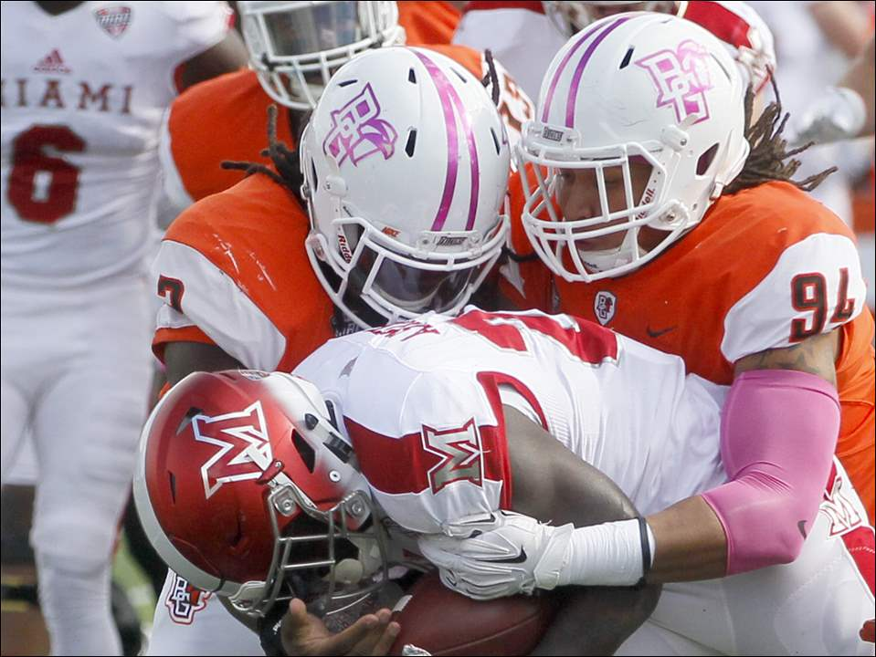 Miami's Alonzo Smith is brought down on the run by Bowling Green's Armani Posey, left, and David Konowalski.