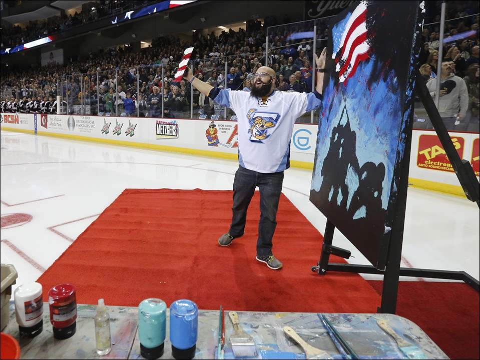 Greenville, South Carolina artist Joe Everson completes a live action painting while he finishes singing the National Anthem before the Toledo Walleye play the Brampton Beast during their home opener Saturday at the Huntington Center. The feat was replayed on ESPN early Sunday morning.