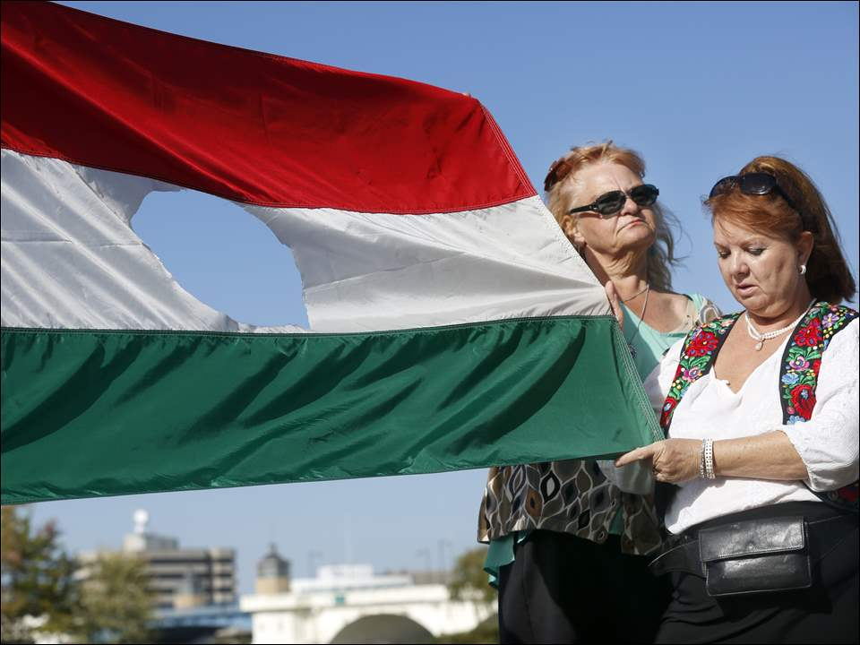 Hilde Daugherty, left, and Katalin Rezbanyay Albring, right, hold a Hungarian flag with a large hole in the center as the symbol of the revolution during a wreath-laying ceremony in International Park.