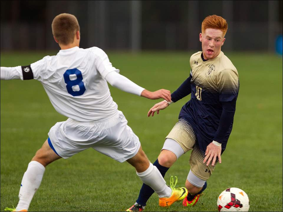 St. John's forward Zachary Buescher dribbles the ball around Findlay midfielder Todd Federici.