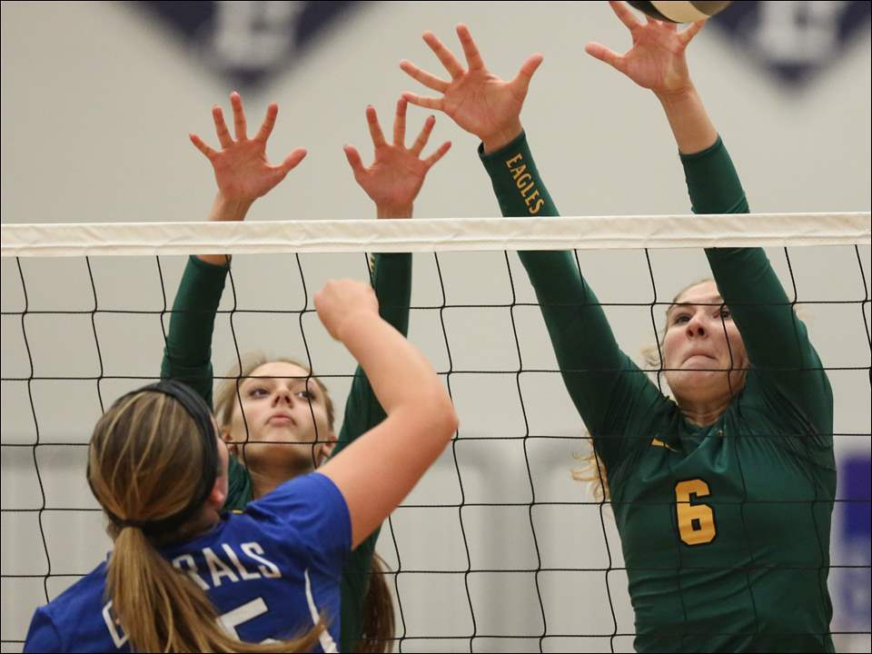 Clay's Mallory Ladd, right, and Madison Hornyak, left, defend the net against  Anthony Wayne's Maddy Pollard.