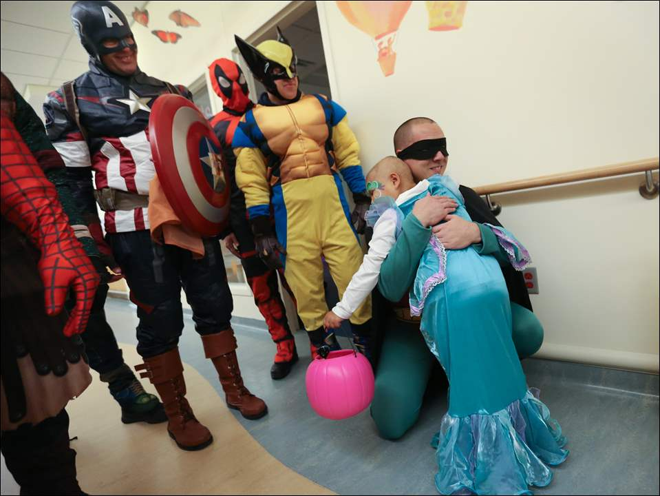 Selina Hernandez, 4, of Defiance, Ohio, hugs Officer Ben Tsou, dressed as cartoon superhero Robin at ProMedica Toledo Children's Hospital. Looking on are Officer Robert Orwig, as Captain America, Sgt. William Shaner, as Spider-Man, and Officer Robert Reed, as Wolverine.