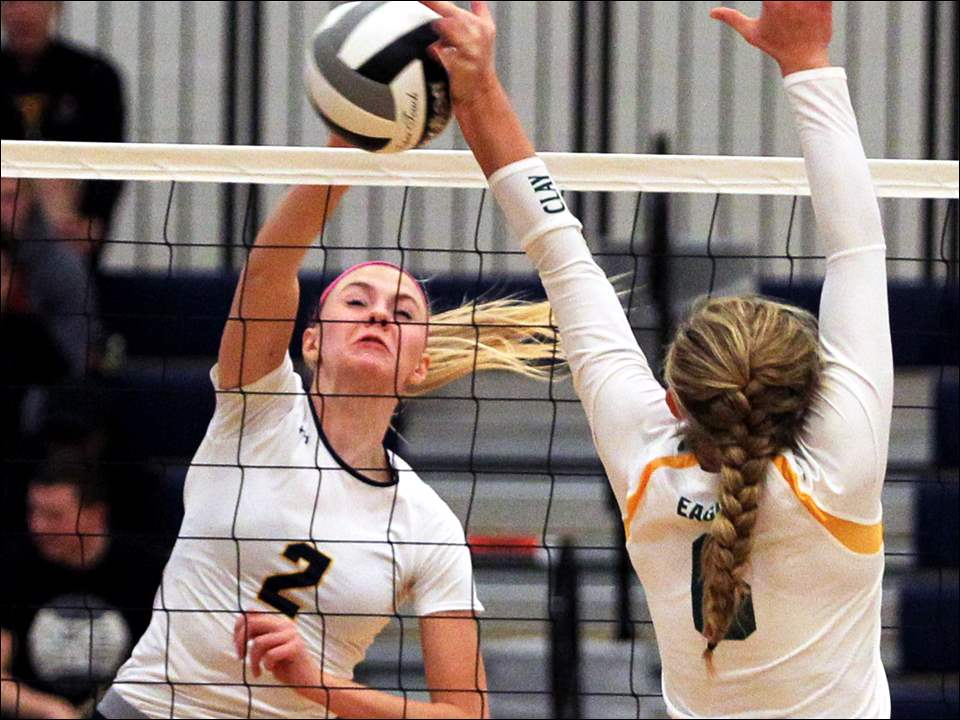 Notre Dame middle hitter Ally Speweik spikes the ball into the hand of Clay outside hitter Mallory Ladd.