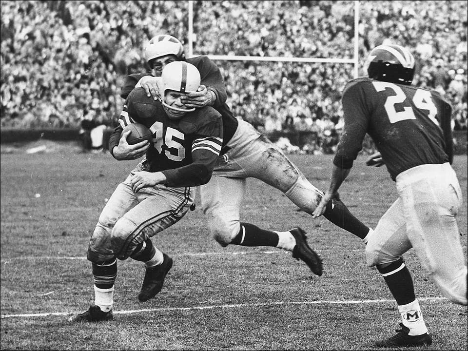 "Buckeye halfback #45 Don Sutherin gets an eyeful as a Wolverine gets a handful during this November 19, 1955 edition of the Ohio State versus Michigan rivalry football game. The tilt was in Ann Arbor for the Big Ten title and the ""gridders"" as they were often called, played before a then record crowd. No penalty would be called on the play. The Buckeyes upset the favored Wolverines, 17-0."