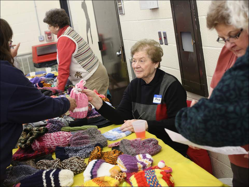 Volunteer Phoebe Goldberg, center, hands a knitted hat to a visitor during Thanksgiving dinner at Christ the King Catholic Church in West Toledo. Parishioners, including Ms. Goldberg, also knitted several hundred hats to give away.