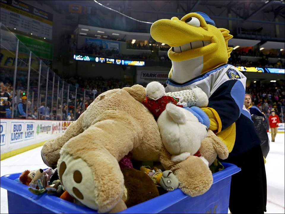 The Toledo Walleye mascot, Spike, wheels a bin full of teddy bears thrown on the ice.
