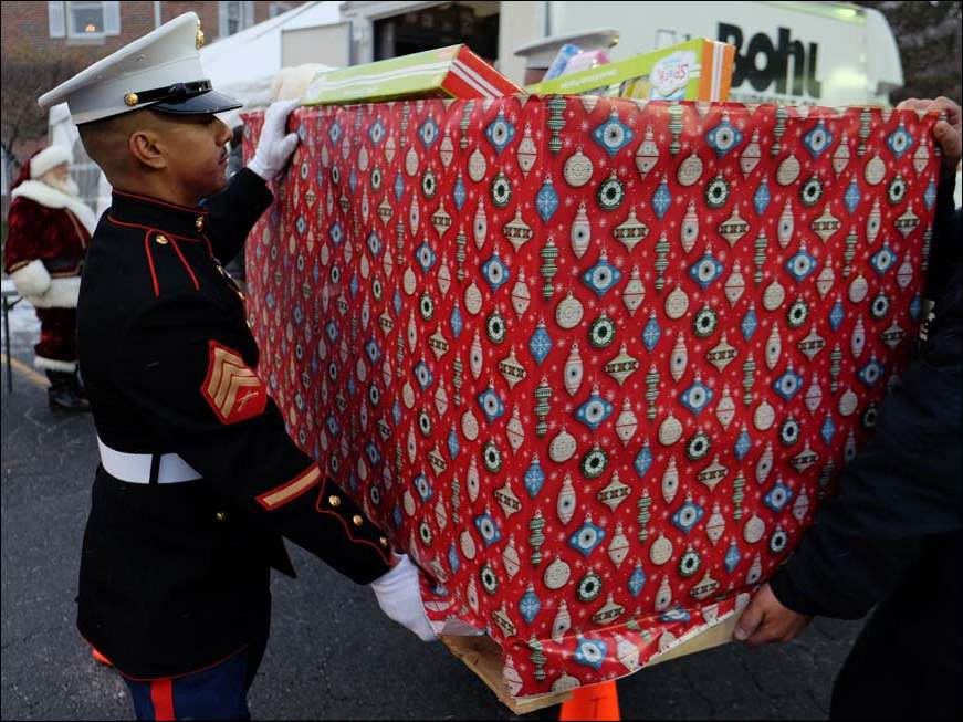 Marine Sgt. Guillermo Amador helps carry donated presents to the Salvation Army truck during the toy drive at WTVG-TV, Channel 13 in Toledo.