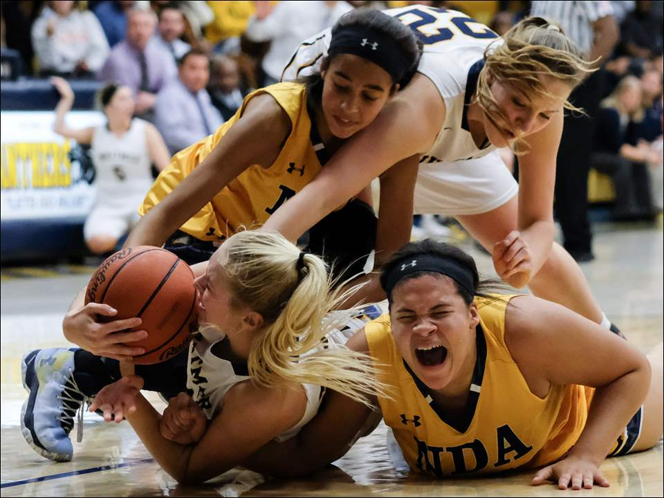 Notre Dame's Krisah Lewis, bottom right, grimaces during a scramble for a loose ball with Whitmer's Rhegyn Blood, bottom left, as Notre Dame's Ashley Barron, top left, and Whitmer's Bryce Blood assist.