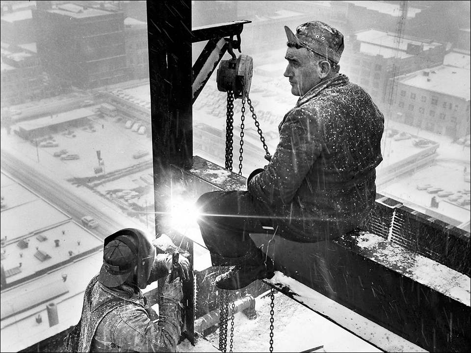 Winter weather has moved in with gusto, making it feel more like the holiday season. But for those who spend most of their workday outside, the blustery winds and snow may not receive such a warm welcome.  Toledo Blade photographer Bob Jacobs took this shot on February 29, 1956, and it makes you feel cold with just a glance. Steve Kertesz of Toledo is astride the girder and Lloyd Caldwell of Curtice is manning the torch. Both were steel workers with the A. B. Bentley Construction Company and were working on top of the National Bank Building enlarging the superstructure for the elevator shaft. They appeared unaffected by the cold, though temperatures that day in Toledo were in the mid-30s with a trace of snow.