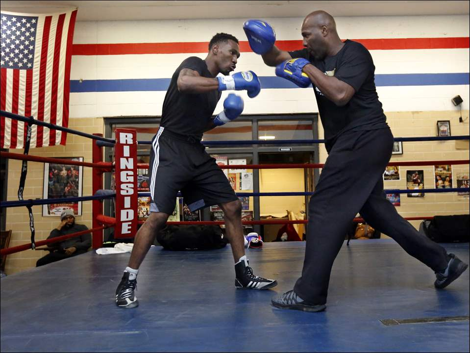 Robert Easter, Jr., Toledo's IBF lightweight champion, left, works out with his father Robert Easter, Sr., right, at the Glass City Boxing Gym.