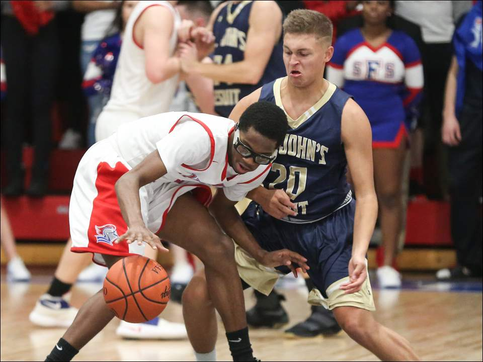 St. Francis player Jakiel Wells, left, drives against  St. John's defender Blake Williams.