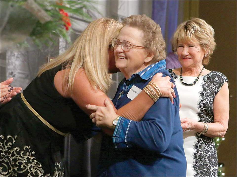 2017 Outstanding Citizen winner Shirley Woessner gets a hug, as 2016 winner Barbara Sanchez looks on, during the annual meeting and dinner.