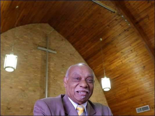 The Rev. Rose in the sanctuary of Serenity Christian Church. A member of the previous congregation that owned the church said that the ceiling was like the hull of a shape used by slavers.