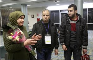 Ghada, left, describes her hope to be reunited with her youngest sons now that she, her husband Khaled, center, and their eldest son Fadi have safely arrived in Toledo.