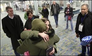 Kathy Savage of Toledo, center, hugs refugee Ghada, who declined to give her last name, shortly after Ghada, her husband Khaled, right, and their eldest son, Fadi, not pictured, arrived at Toledo Express Airport.