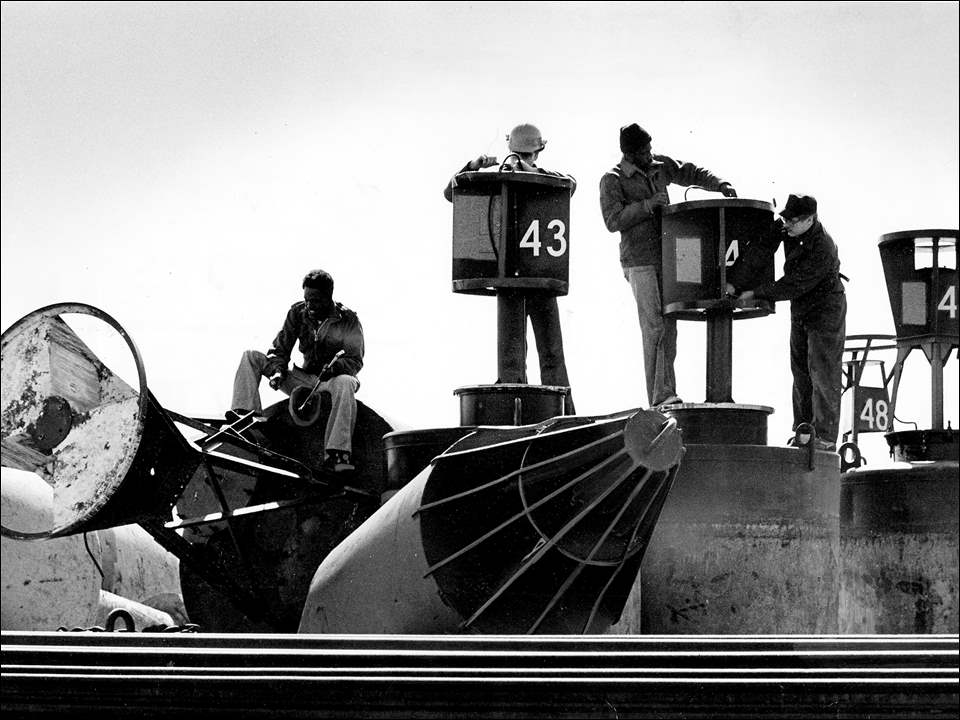 Coast Guardsmen got to work preparing buoys for Lake Erie. Blade photographer Don Flory captured the men getting things ready on March 12, 1979.  From left to right are Coast Guardsmen Dava Jones, Michael Lafko, Darrell Banks, and Mark Krainock.  The floating buoys were checked at the Bay View Park Coast Guard station in Toledo. The work was part of an annual ritual of preparing channel markers for another year of shipping activity.  The buoys were taken ashore late each year, then scraped, painted, and repaired. When the ice was gone from Lake Erie, the markers were dropped in place to guide lake and ocean ships through the western end of the lake and into port.